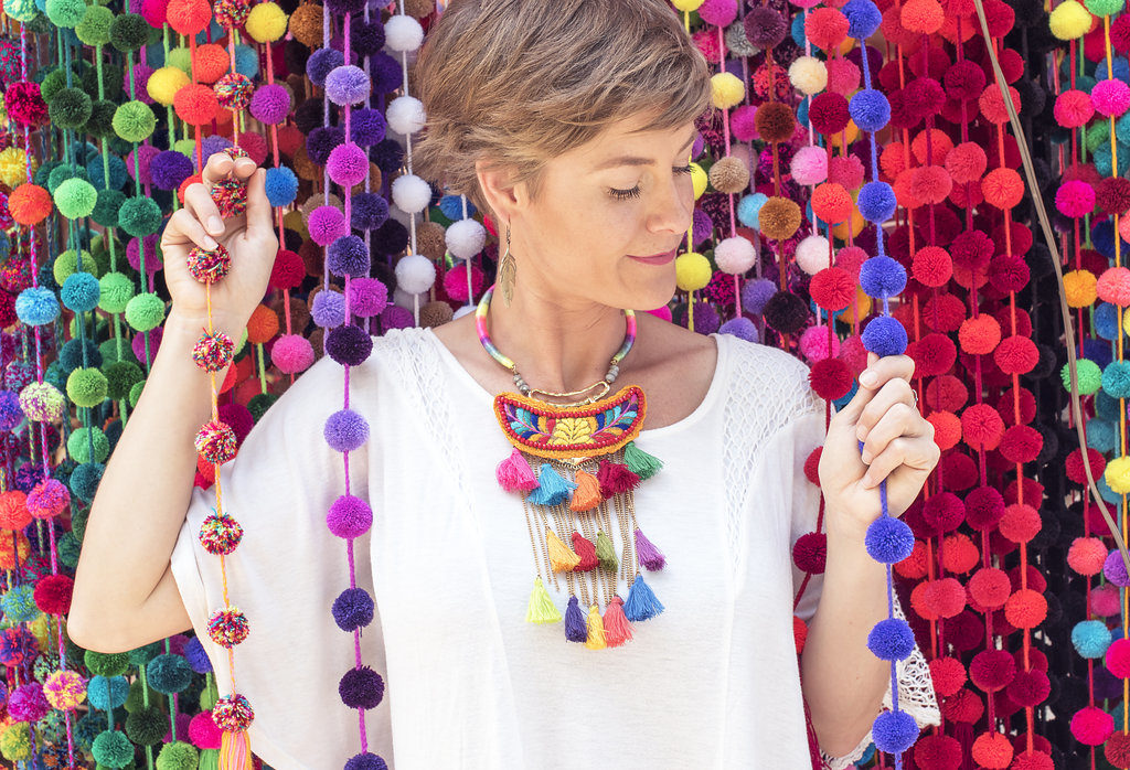 Ava poses with colorful pom poms in a market in San Cristobal de Las Casas, Chiapas, Mexico. She is wearing a stylish necklace and blouse. She is inviting women to sign up for her online consulting and coaching using styling and design for empowerment.